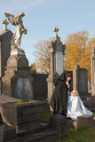 Young widow. In Victorian dress sitting on a tombstone Stock Images