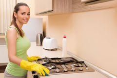 The young wife cleaning kitchen holding bottle Stock Photo