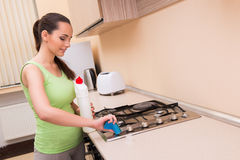The young wife cleaning kitchen holding bottle Royalty Free Stock Photo