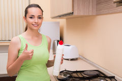 The young wife cleaning kitchen holding bottle Stock Photography
