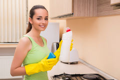 The young wife cleaning kitchen holding bottle Royalty Free Stock Images