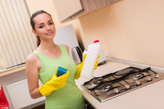 The young wife cleaning kitchen holding bottle Stock Images