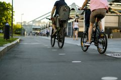 Young wife and husband riding bikes in the europe street during summer season royalty free stock photography