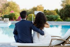 Young wife and husband sitting at the pool Stock Photos