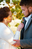 Young wife pinning buttonhole flowers to groom's coat Royalty Free Stock Image