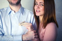 Young wife pulls out dollar bills from her husband`s shirt pocket, husband grabbed her hand and does not allow to pull. Young wife pulls out dollar bills from royalty free stock image
