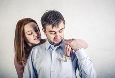 Young wife pulls out dollar bills from her husband`s shirt pocket, the husband grabbed her hand and does not allow to pull out th. Young wife pulls out dollar stock photo