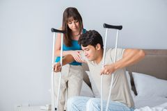 The young wife supporting husband on crutch after injury. Young wife supporting husband on crutch after injury Stock Photography