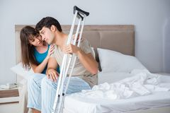 The young wife supporting husband on crutch after injury. Young wife supporting husband on crutch after injury Royalty Free Stock Photography