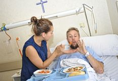 Young wife trying to feed his reluctant husband lying in bed at hospital room ill after suffering accident. Young wife trying to feed his husband lying in bed at Royalty Free Stock Photography