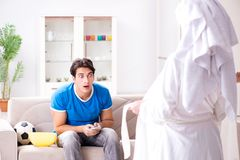 Young wife is trying to seduce husband from watching football an. D tv Royalty Free Stock Image