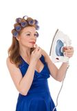 Young wife using iron as mirror Stock Photo