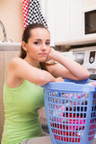 The young wife woman washing clothes near machine Stock Images