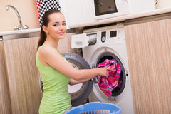 The young wife woman washing clothes near machine Royalty Free Stock Images