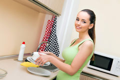 The young wife woman washing dishes in kitchen Stock Image