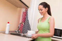The young wife woman washing dishes in kitchen Stock Photography