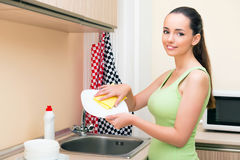 The young wife woman washing dishes in kitchen Royalty Free Stock Images