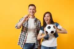 Young win couple, woman man, football fans holding bitcoin, metal golden coin, soccer ball, cheer up support team. Isolated on yellow background. Sport bet stock photos
