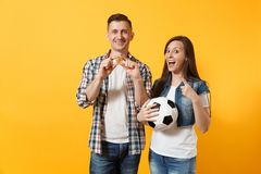 Young win couple, woman man, football fans holding bitcoin, metal golden coin, soccer ball, cheer up support team. Isolated on yellow background. Sport bet royalty free stock photo