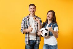 Young win couple, woman man, football fans holding bitcoin, metal golden coin, soccer ball, cheer up support team. Isolated on yellow background. Sport bet royalty free stock image
