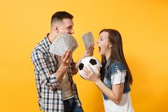 Young win couple, woman man, football fans holding bundle of dollars, cash money, soccer ball, cheer up support team. Young win couple, women man, football fans royalty free stock photos