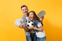 Young win couple, woman man, football fans holding bundle of dollars, cash money, soccer ball, cheer up support team. Young win couple, women man, football fans royalty free stock photography