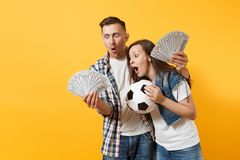 Young win couple, woman man, football fans holding bundle of dollars, cash money, soccer ball, cheer up support team. Young win couple, women man, football fans stock photos