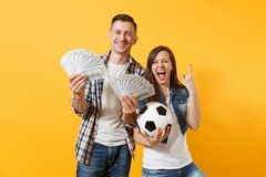 Young win couple, woman man, football fans holding bundle of dollars, cash money, soccer ball, cheer up support team. Young win couple, women man, football fans royalty free stock images