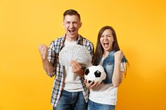 Young win couple, woman man, football fans holding bundle of dollars, cash money, soccer ball, cheer up support team. Young win couple, women man, football fans stock photography