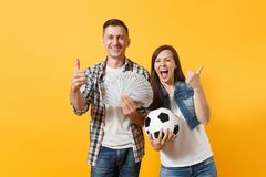 Young win couple, woman man, football fans holding bundle of dollars, cash money, soccer ball, cheer up support team. Isolated on yellow background. Sport bet royalty free stock image