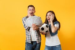 Young win couple, woman man, football fans holding bundle of dollars, cash money, soccer ball, cheer up support team. Young win couple, women man, football fans stock image