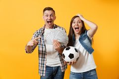 Young win couple, woman man, football fans holding bundle of dollars, cash money, soccer ball, cheer up support team. Young win couple, women man, football fans stock images