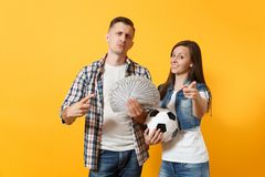 Young win couple, woman man, football fans holding bundle of dollars, cash money, soccer ball, cheer up support team. Young win couple, women man, football fans stock photo