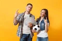 Young win couple, woman man, football fans holding bundle of dollars, cash money, soccer ball, cheer up support team. Isolated on yellow background. Sport bet royalty free stock photos