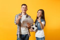 Young win couple, woman man, football fans holding bundle of dollars, cash money, soccer ball, cheer up support team. Isolated on yellow background. Sport bet stock images
