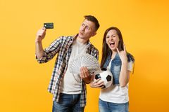 Young win couple, woman man, football fans holding bundle of dollars money, credit card, soccer ball, cheer up support. Young win couple, women man, football stock images