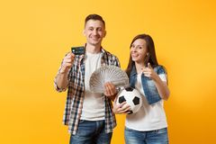 Young win couple, woman man, football fans holding bundle of dollars money, credit card, soccer ball, cheer up support. Young win couple, women man, football royalty free stock photo