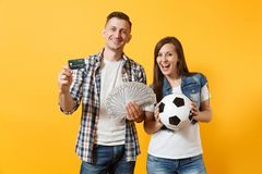 Young win couple, woman man, football fans holding bundle of dollars money, credit card, soccer ball, cheer up support. Team isolated on yellow background royalty free stock photography