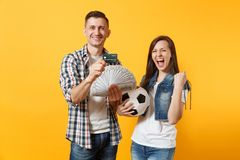 Young win couple, woman man, football fans holding bundle of dollars money, credit card, soccer ball, cheer up support. Team isolated on yellow background stock photography