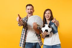 Young win couple, woman man, football fans holding bundle of dollars, cash money, soccer ball, cheer up support team. Young win couple, women man, football fans royalty free stock image