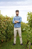 Young winemaker portrait. Full length portrait of young winemaker standing at vineyards while looking at camera and smiling. Small business Royalty Free Stock Photos