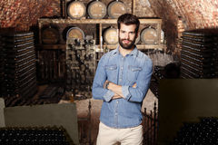 Young winemaker. Portrait of young winemaker standing in his wine cellar in front of barrel and looking at camera. Small business Stock Photography