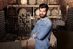 Young winemaker. Portrait of young winemaker standing in his wine cellar in front of barrel and looking at camera. Small business Stock Photos