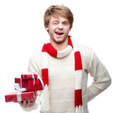 Young winking man holding christmas gifts Royalty Free Stock Photo
