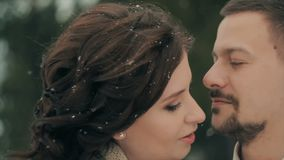 Young winter couple against blurred christmas snowfall on Winter Day. stock video footage