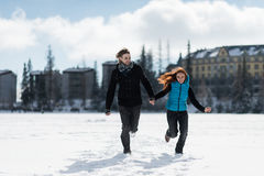 Young winter couple holding hands and running Royalty Free Stock Photography