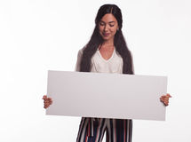 Young wistful woman showing presentation, pointing on placard Royalty Free Stock Photo