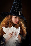 Young witch. In a hat Royalty Free Stock Photos