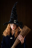 Young witch. Red-haired young witch with broom Royalty Free Stock Photo