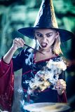 Magic Potion In The Goblet. Young witch with angry evil face holds a goblet with magic potion in one and magic wand in the other hand Stock Photos